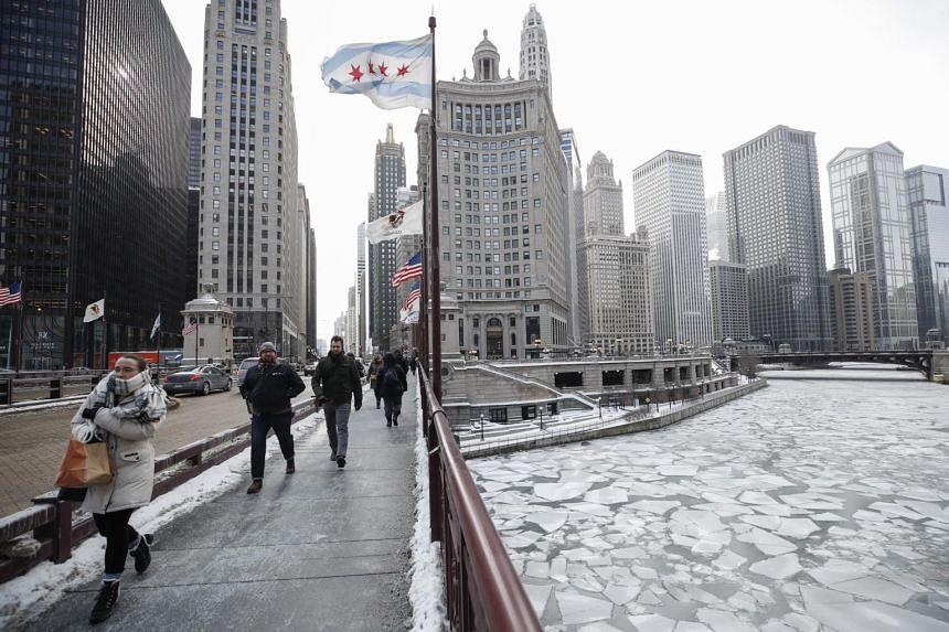 Pedestrians walk along Michigan Avenue above the frozen Chicago River in Chicago, US, on Jan 29, 2019.