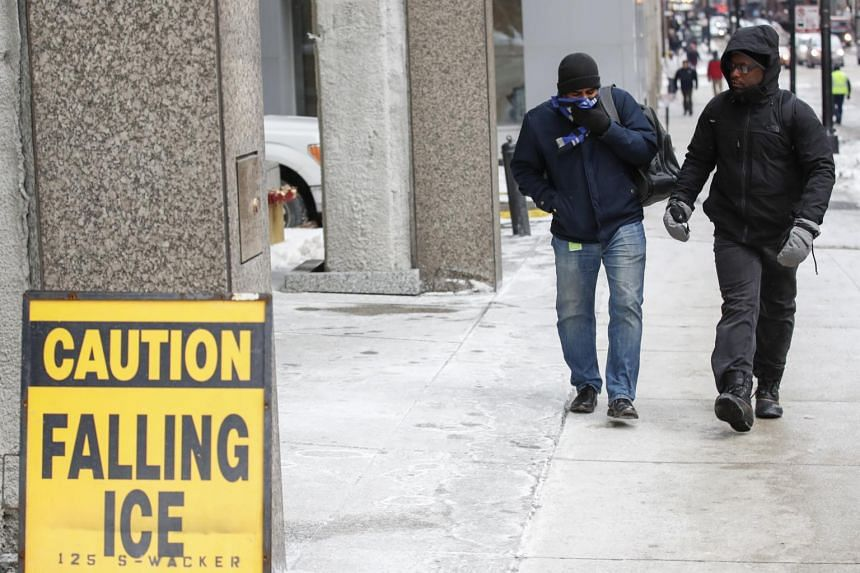 Men walk by a sign warning of falling ice in Chicago, USA, on Jan 29, 2019.