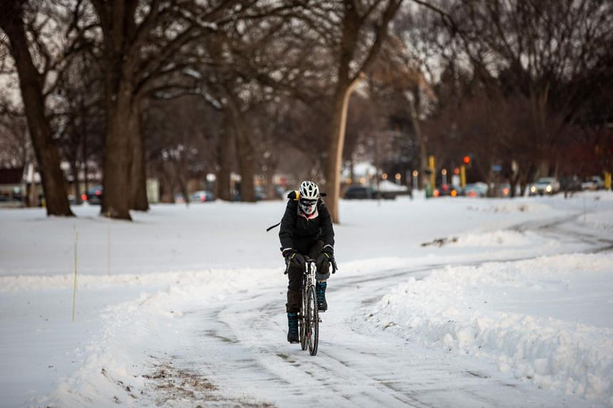 A cyclist passes through heavy frost in Nokomis parkway, Minneapolis, as temperatures in the area dipped below freezing overnight in Minnesota on Jan 29, 2019.
