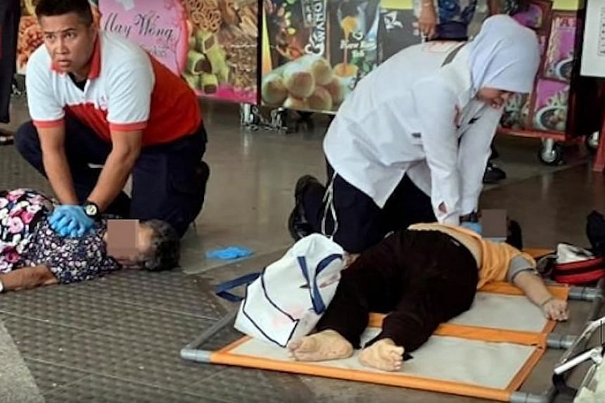 Two victims at the Kuala Lumpur market stampede receiving aid. Almost 1,000 people were there to get free food coupons.