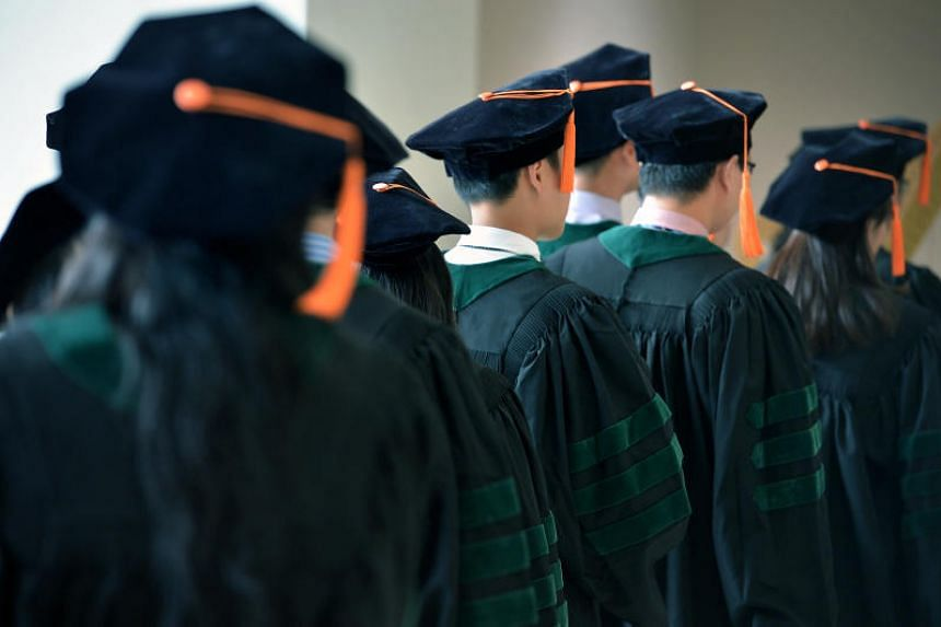 File photo showing university students in Singapore attending a graduation ceremony.