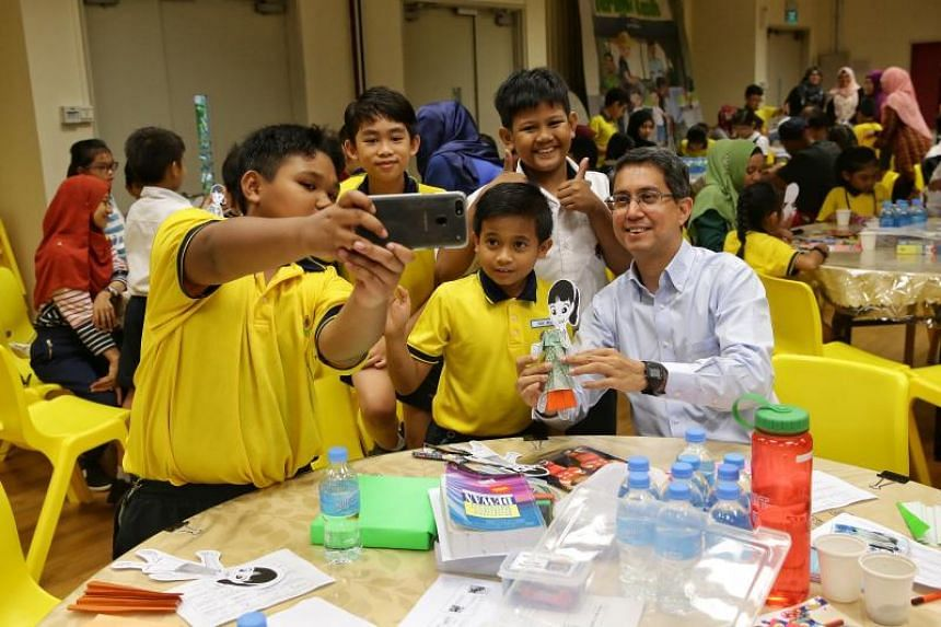 Chairman of the Malay Language Learning and Promotion Committee Muhammad Faishal Ibrahim taking a wefie with pupils during a workshop on reading on Jan 30, 2019.
