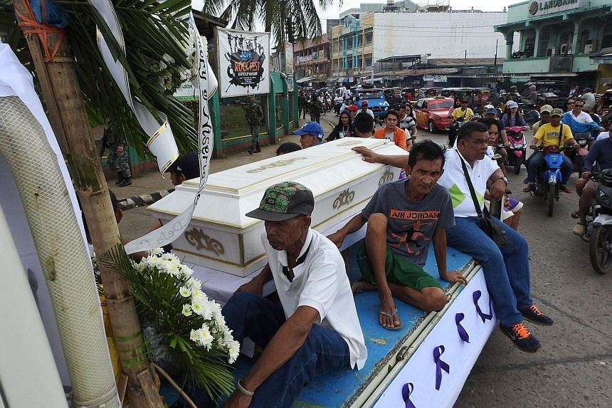 Mourners sitting on a hearse during the funeral procession for a victim of the Jan 27 church bombing in Jolo, in Sulu province.