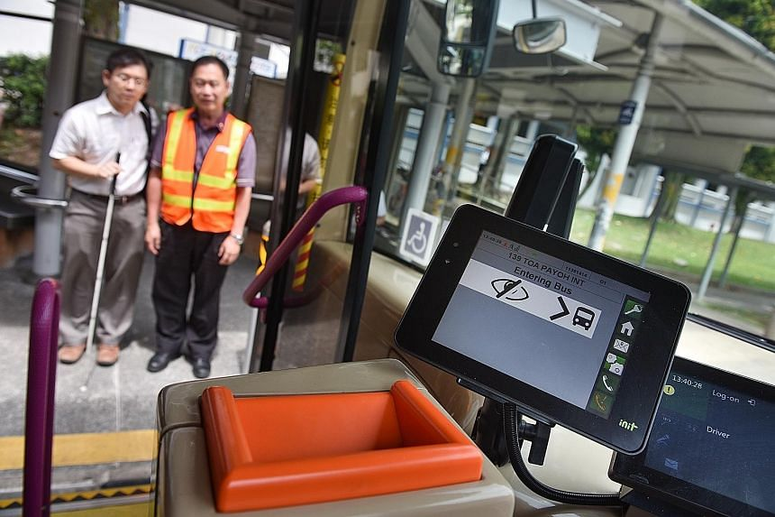 A wheelchair-bound commuter using the app to alert the bus driver that he wants to board the bus at the bus stop. Above: Mr Chong Kwek Bin getting ready to board the bus with the bus driver's help. Left: A sign on the bus about a hearing-aid feature