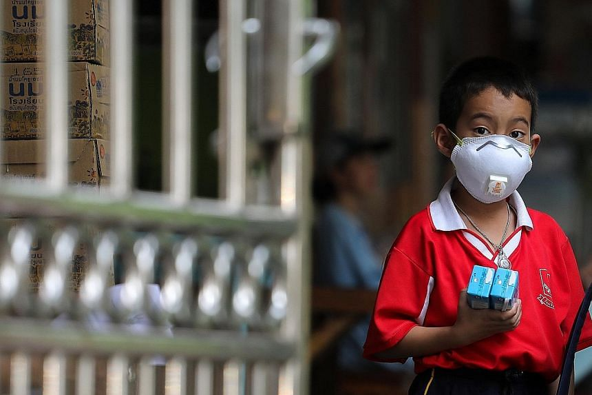 A pupil wearing a mask in Bangkok yesterday. More than 400 public schools in the Thai capital were closed at noon yesterday due to pollution.