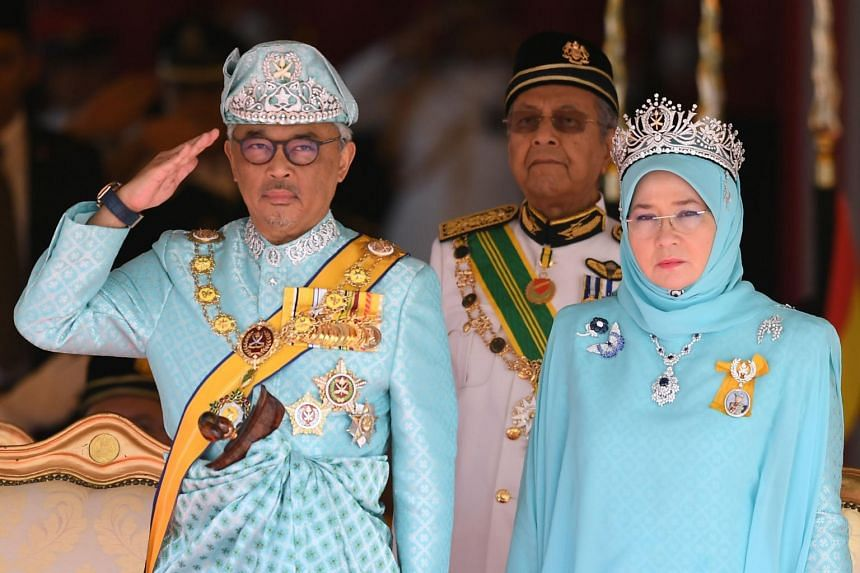 Sultan Abdullah Ri'ayatuddin with his wife, Tunku Azizah Aminah Maimunah Iskandariah Sultan Iskandar, as he salutes the guard of honour during an official welcome at Parliament Square in Kuala Lumpur on Jan 31.