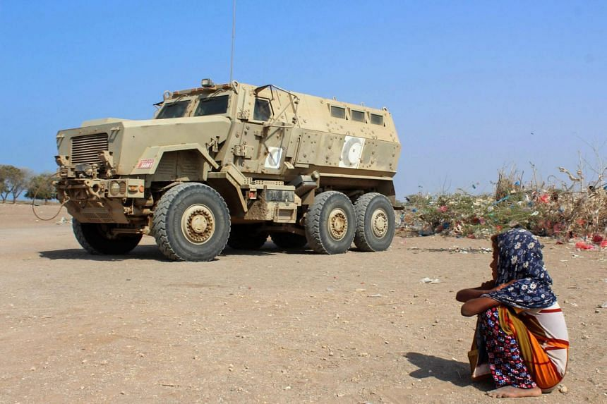A displaced Yemeni girl sits next to an armoured military vehicle at a camp in the Khokha district of the western province of Hodeida, on Jan 21, 2019.