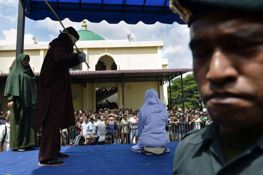An 18-year-old Indonesian woman is caned in public in Banda Aceh on Jan 31, 2019, as punishment after being caught cuddling with her boyfriend.