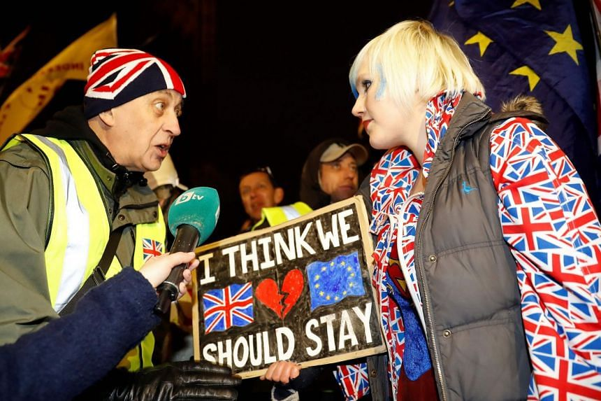 A pro-Brexit activist (left) remonstrates with an anti-Brexit activist outside of the Houses of Parliament in London.