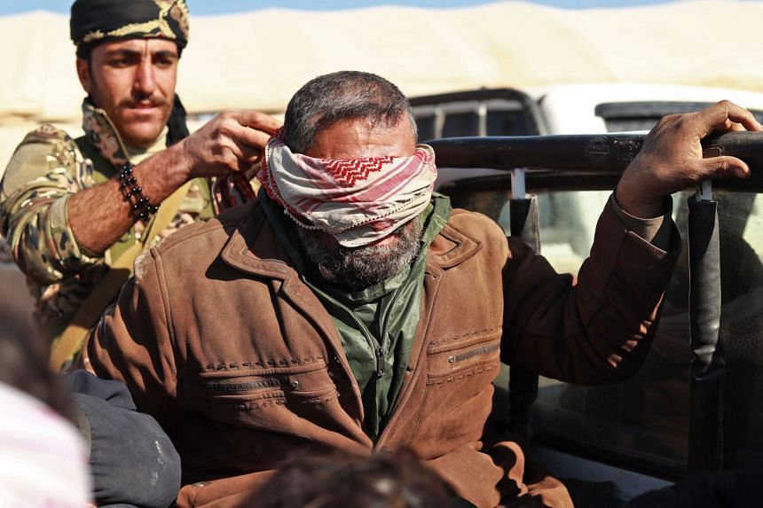 An alleged ISIS militant sits blindfolded in the back of a pickup truck after he was taken into custody by SDF forces, Jan 30, 2019.