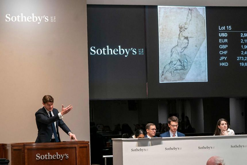 """A Sotheby's auctioneer takes bids on Rubens' """"Nude Study of a Young Man with Raised Arms""""."""