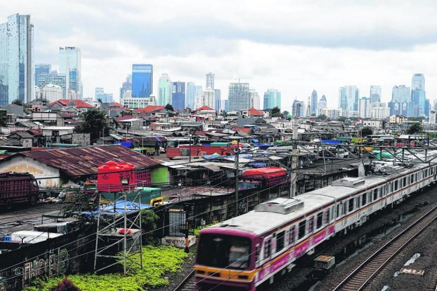 A commuter train is seen against the backdrop of high-rise buildings at Tanah Abang district in Jakarta, Indonesia, on Jan 19, 2018.