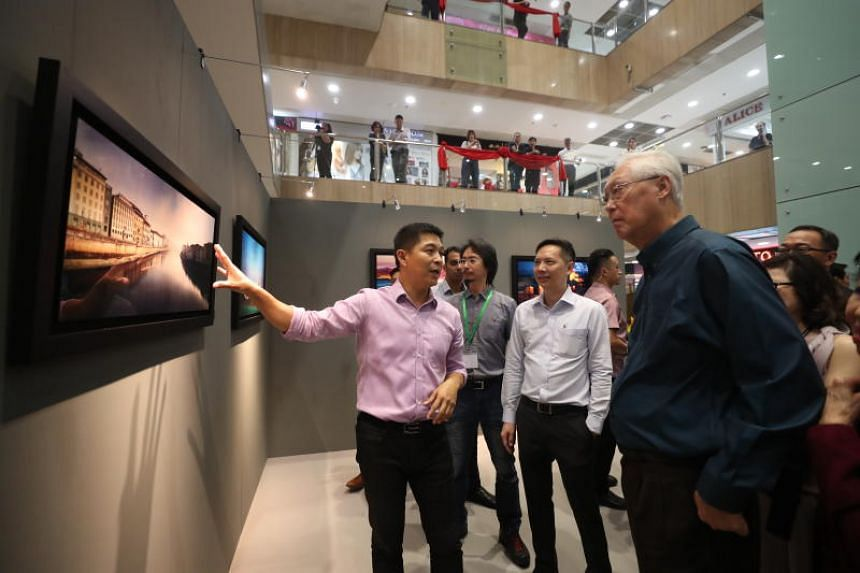 Speaker of Parliament Tan Chuan-Jin introducing a photo to ESM Goh Chok Tong (in blue) at his exhibition titled Our Place in the World.