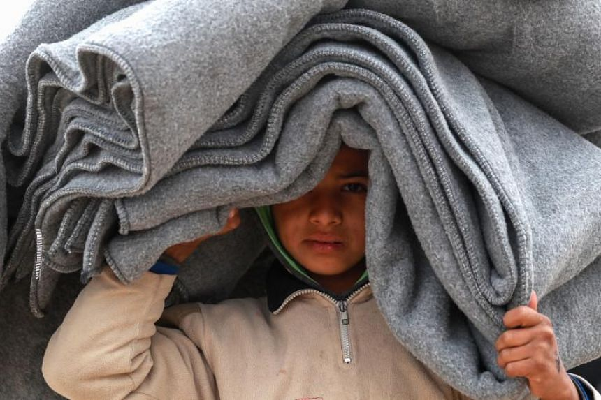 A Syrian boy carries blankets over his head inside a camp in al-Hol in northeastern Syria, on Dec 8, 2018.