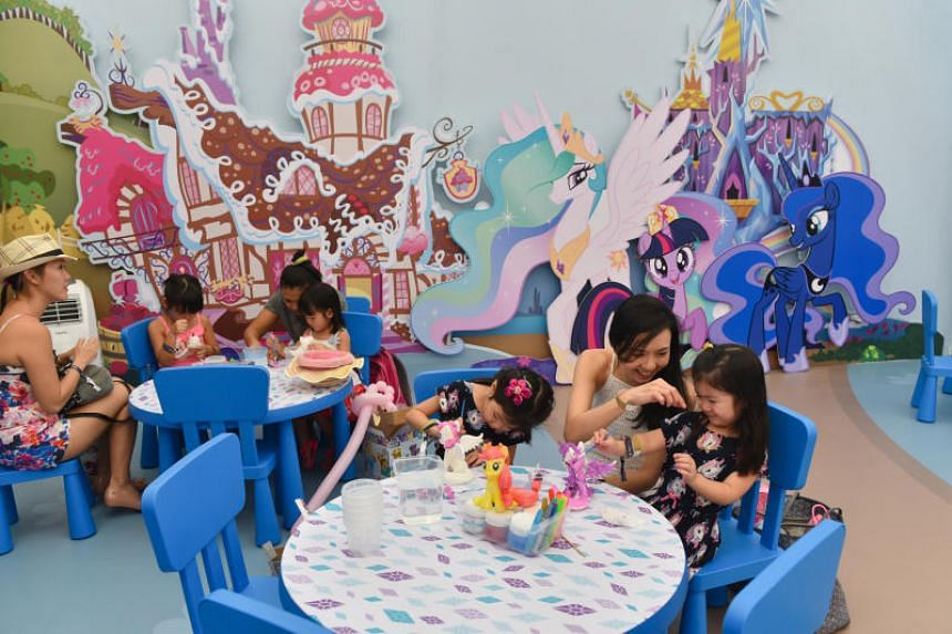 Families painting My Little Pony figurines in My Little Pony Rainbow Kingdom at the Toybox Powered by Hasbro carnival.