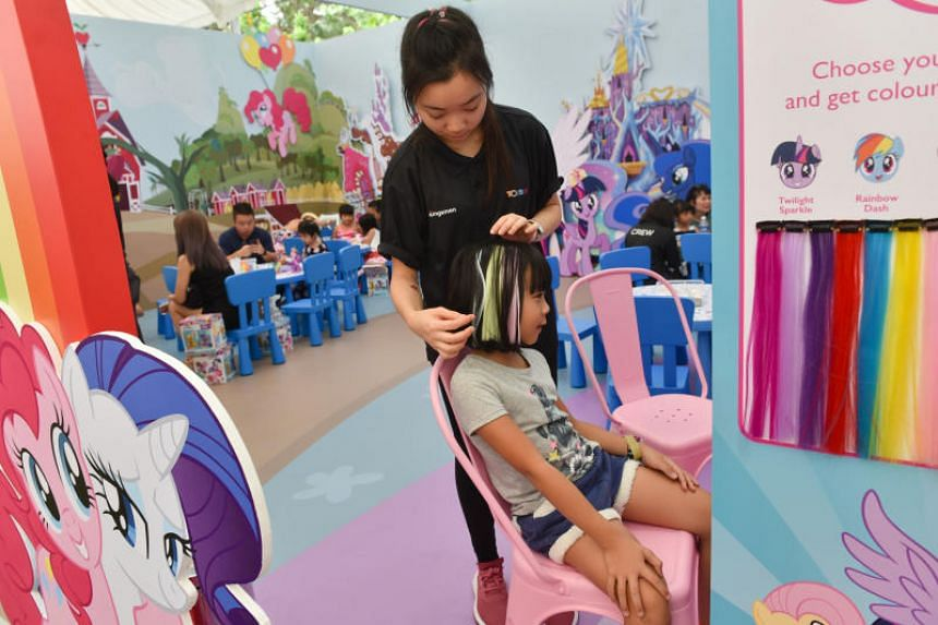 Kayla Lee, 7, sits in a makeup booth in My Little Pony Rainbow Kingdom and receives hair extensions with colours inspired from the franchise's characters from a staffer.