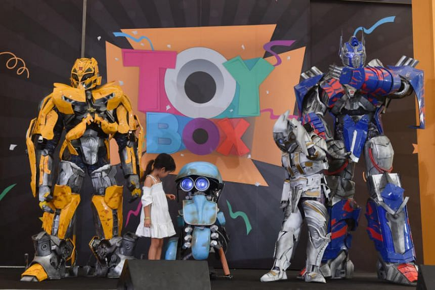 Leia Zhang, 6, goes up on stage to pose with mascots from the Transformers Live show during the meet and greet session at the Toybox Powered by Hasbro carnival.