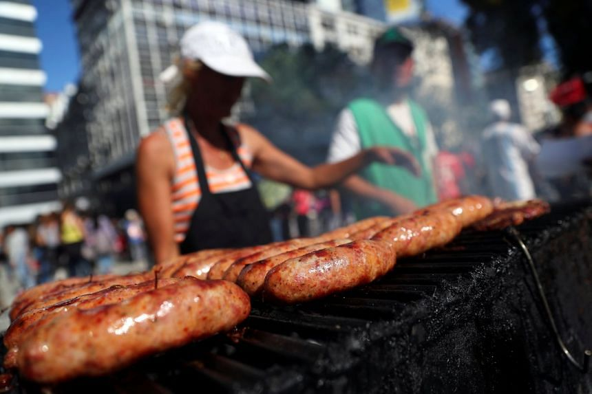 A woman grilling sausages at a street stand in Buenos Aires, Argentina.