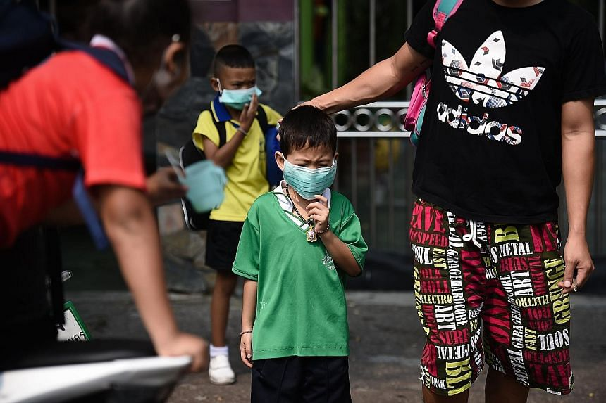 Children wearing face masks leaving their school early due to air pollution in Bangkok on Wednesday.