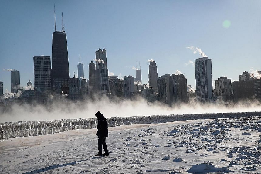 A man walking along the frozen lakefront in Chicago, Illinois. Officials warned about the risk of almost instant frostbite on what could be the city's coldest day, as Wednesday night's temperature was projected to dip to minus 31 deg C due to rare po