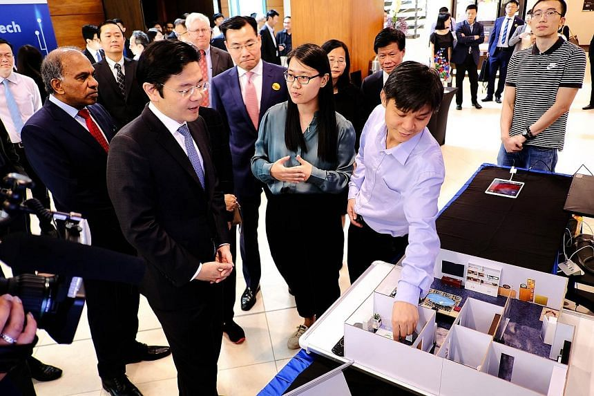 Mr Lawrence Wong (front row, left), Second Minister for Finance and National Development Minister, viewing an NTU research project that leverages on cutting-edge technology such as the Internet of Things, at the opening ceremony yesterday of the rese