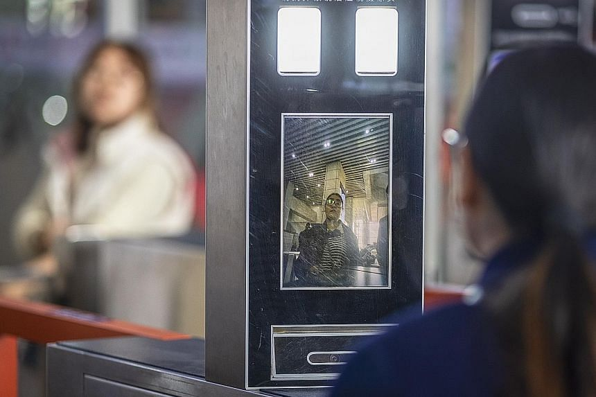 Above: Policemen patrolling with a security robot at a railway station in Shenzhen last week. Left: A woman having her face scanned by a ticket machine at a railway station in Guangzhou on Sunday.