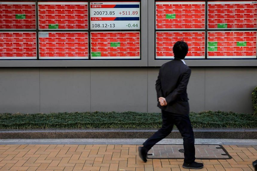 A man looks at an electronic board showing the Nikkei stock index outside a brokerage in Tokyo, Japan.