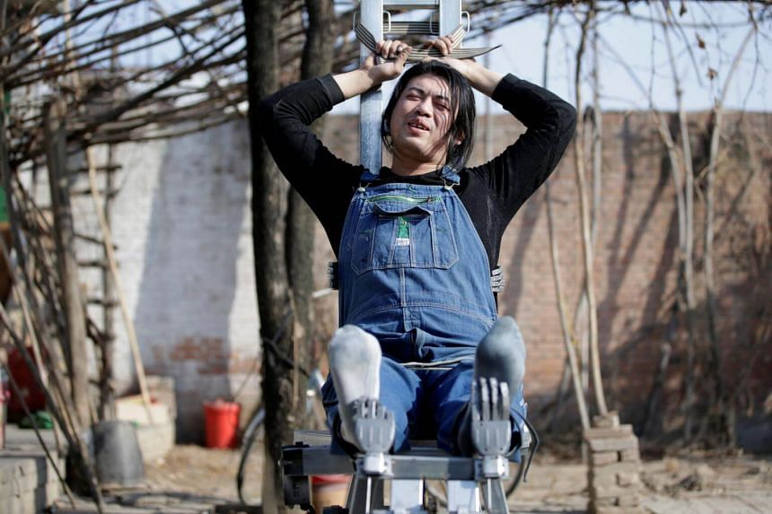 """Mr Geng Shuai poses on his invention """"happy chair"""", a workout bench with robotic arms to tickle the underarms and the feet, outside his workshop in Yangcun village, Hebei province, China, on Jan 22, 2019."""