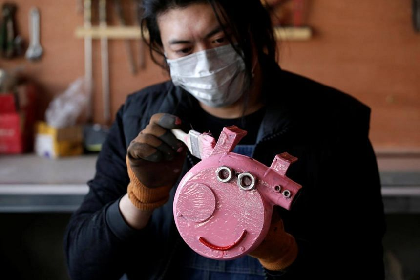 Mr Geng works on a sculpture depicting animated series character Peppa Pig, made of an air blower, at his workshop in Yangcun village, Hebei province, China, on Jan 22, 2019.