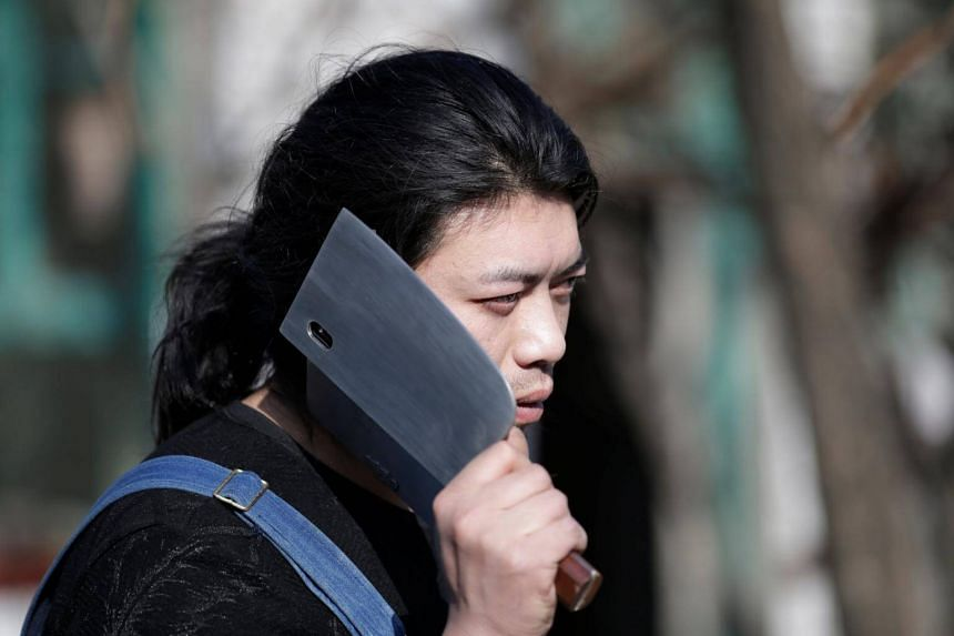 Mr Geng with his invention, a mobile phone case in the shape of a knife, outside his workshop.