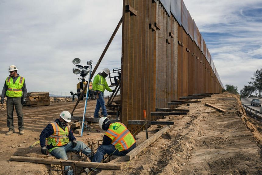 Contractors work on expanding a portion of the border wall between San Diego, California, and Tijuana, Mexico, on Dec 4, 2018.