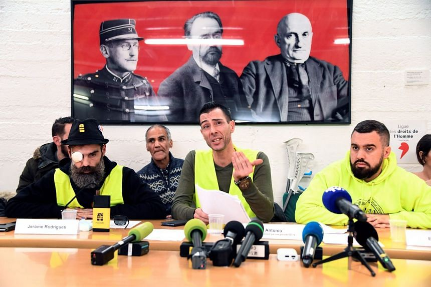 """Jerome Rodrigues (left) and Eric Drouet (right), two of the leading figures of the """"yellow vests"""" movement, hold a press conference on Jan 30, 2019, in Paris with activist Antonio (centre), who claims he was badly injured by a GLI-F4 tear gas and stu"""