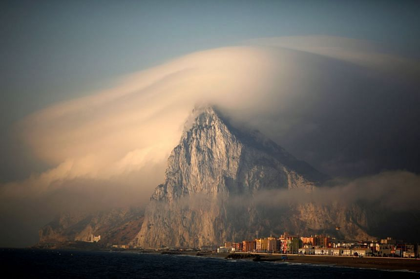 A cloud partially covers the tip of the Rock of the British territory of Gibraltar at sunrise from La Atunara port.