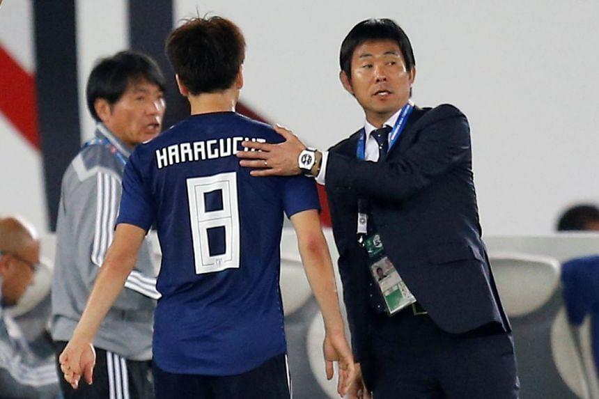 Japan's Genki Haraguchi with coach Hajime Moriyasu as he is substituted.