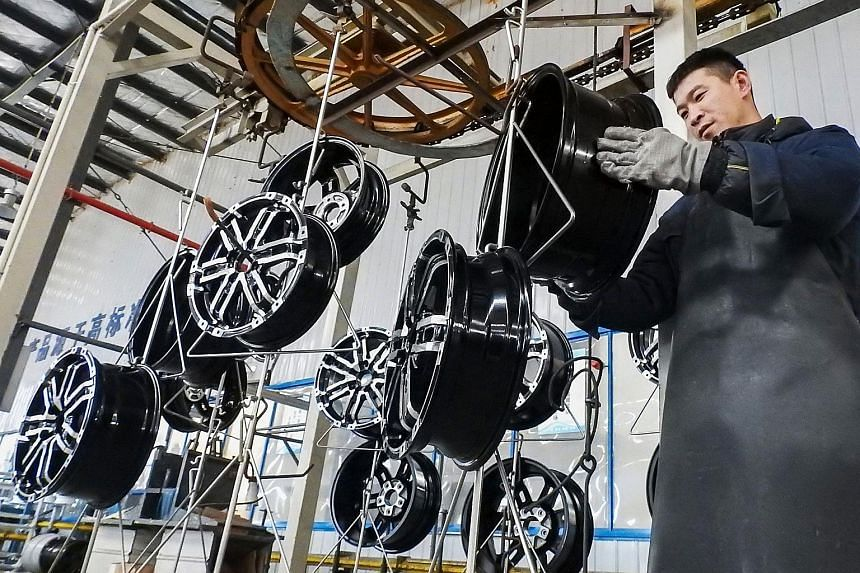A worker checks wheels at a factory in Lianyungang in China's Jiangsu province. China's manufacturing activity contracted last month, official data showed.