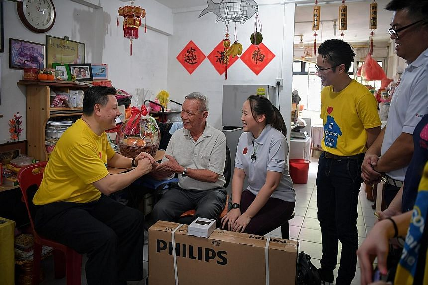 Mr Ben Tan (left), country chief executive officer of Courts Singapore speaking with Mr Ng Ah Ngow, 77, during a home visit on Thursday. With them are Ms Jaena Teo , acting head for the CareElderly programme from Care Community Services Society (CCSS