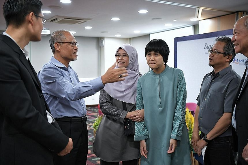 Minister-in-charge of Muslim Affairs Masagos Zulkifli, with Muis chief executive Esa Masood (left) and Special Needs Trust Company chairman Moses Lee (right), speaking with Muis Special Needs Trust Scheme beneficiary Nazurah Noorabidin and her parent