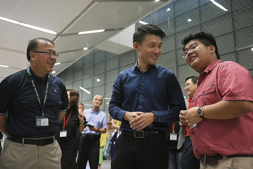 Senior Parliamentary Secretary for Transport Baey Yam Keng (centre) chatting with photographer Isaac Benjamin Ong (right), whose work is featured in the Show The Full Picture exhibition. They were joined at yesterday's launch by LTA deputy chief exec