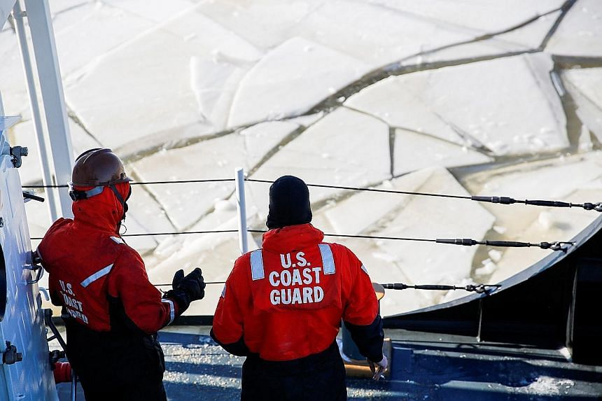 An official of the Salvation Army hugging a homeless person during a cold wellness check-up in Chicago on Thursday. US Coast Guard staff using a boat as an ice breaker on the Hudson River, between the towns of Kingston and Poughkeepsie, in New York,
