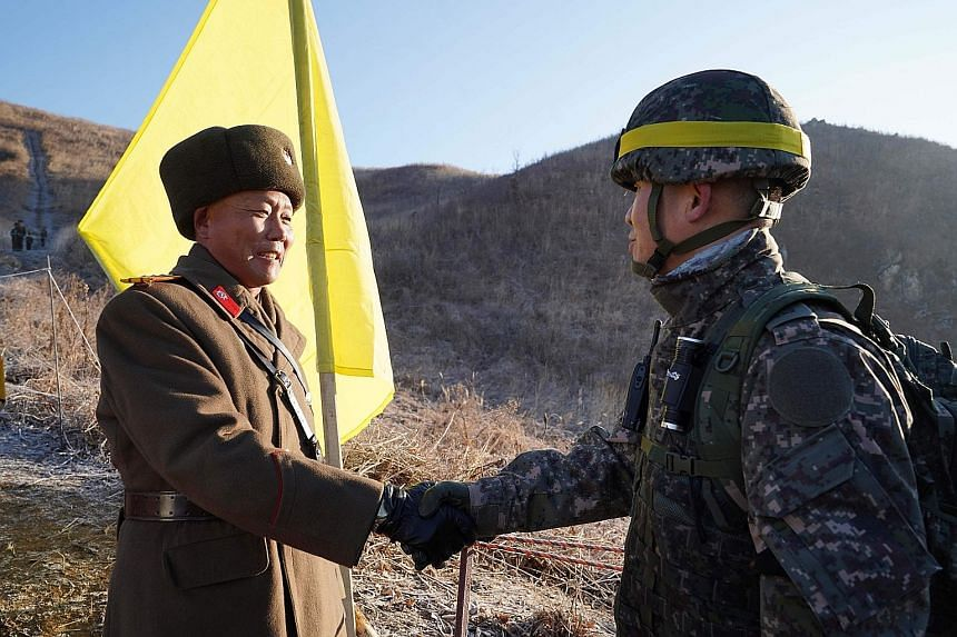 A South Korean soldier (far right) meeting a North Korean one before crossing the Military Demarcation Line last December to inspect a dismantled North Korean guard post inside the Demilitarised Zone dividing the two Koreas in Cheorwon.