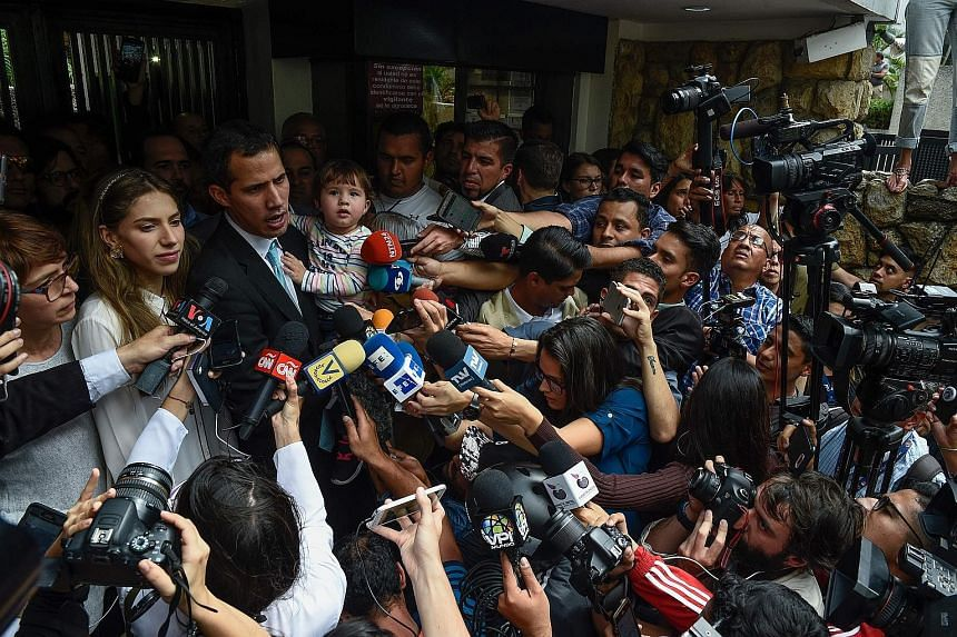 "Opposition leader and self-proclaimed ""acting president"" Juan Guaido, seen here with his daughter Miranda and wife Fabiana Rosales, has accused socialist leader Nicolas Maduro's security forces of going to his home and trying to intimidate his family"