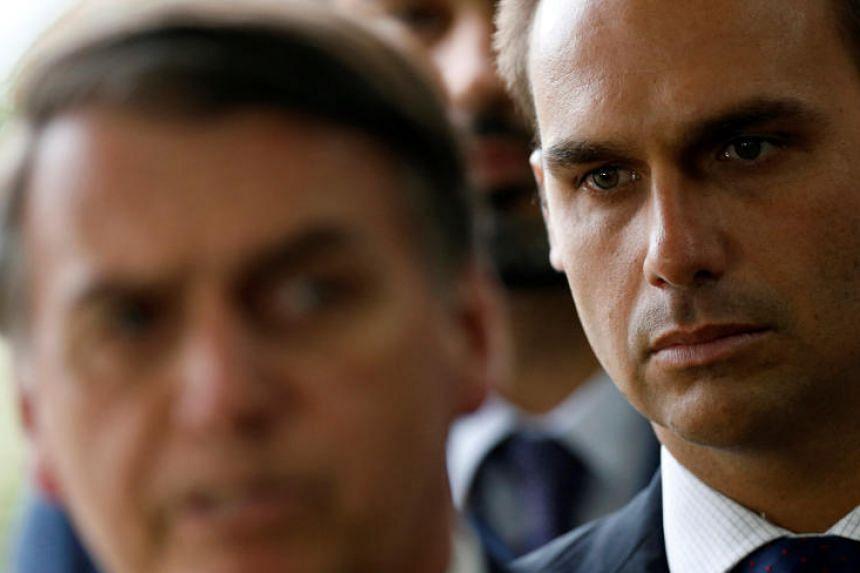 Eduardo Bolsonaro, son of Brazil's President-elect Jair Bolsonaro is seen behind him at the transition government building in Brasilia, Brazil, on Dec 4, 2018.