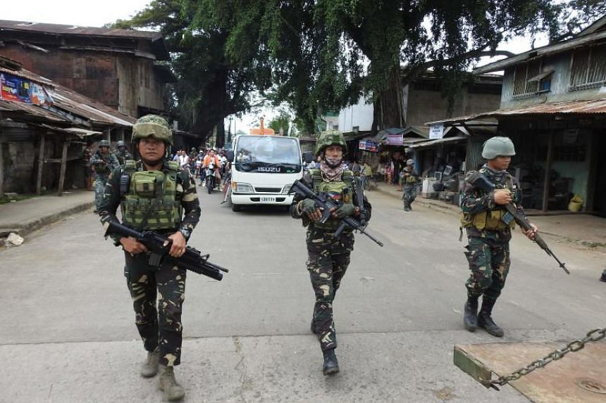 Philippine soldiers escorting a hearse during the funeral procession of a victim killed in the cathedral bombing in Jolo, Sulu province, on the southern island of Mindanao on Jan 30, 2019.