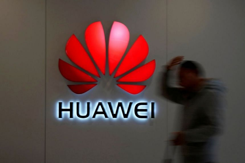 A man walks by a Huawei logo at a shopping mall in Shanghai, China, on Dec 6, 2018.