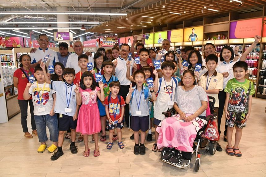 Beneficiaries of the Straits Times School Pocket Money Fund taking a photo with senior NTUC Fairprice staff and FairPrice's chief executive Seah Kian Peng (middle, in white).