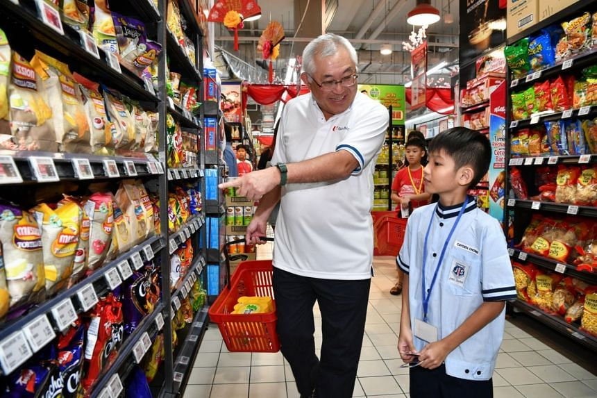 FairPrice Foundation Chairman, Mr Bobby Chin, shops with Cayden Chong, 10, a beneficiary of the Straits Times School Pocket Money Fund.