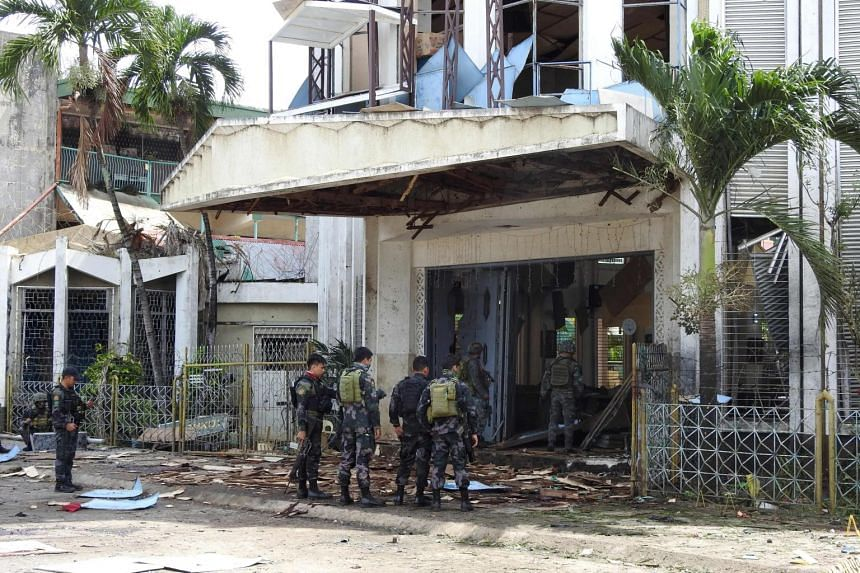 Policemen and soldiers standing outside the bomb-hit church in Jolo, Sulu province, on the southern island of Mindanao, on Jan 27, 2019.