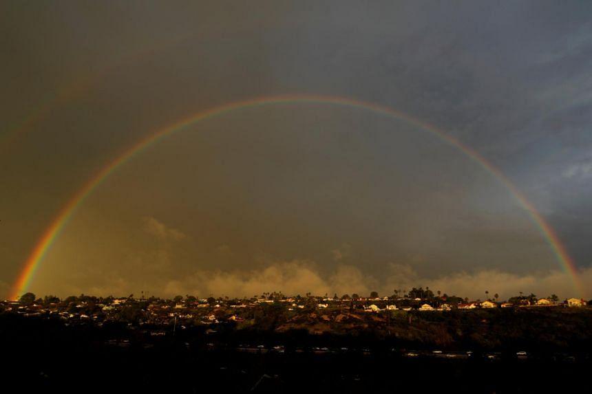 A rainbow appears above homes on a hillside following a rain storm in Encinitas, California, on Jan 31, 2019.