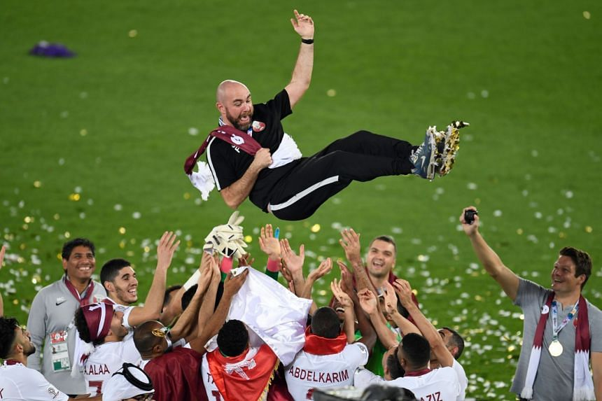 Qatar's coach Felix Sanchez is thrown in the air as his team celebrates their win.
