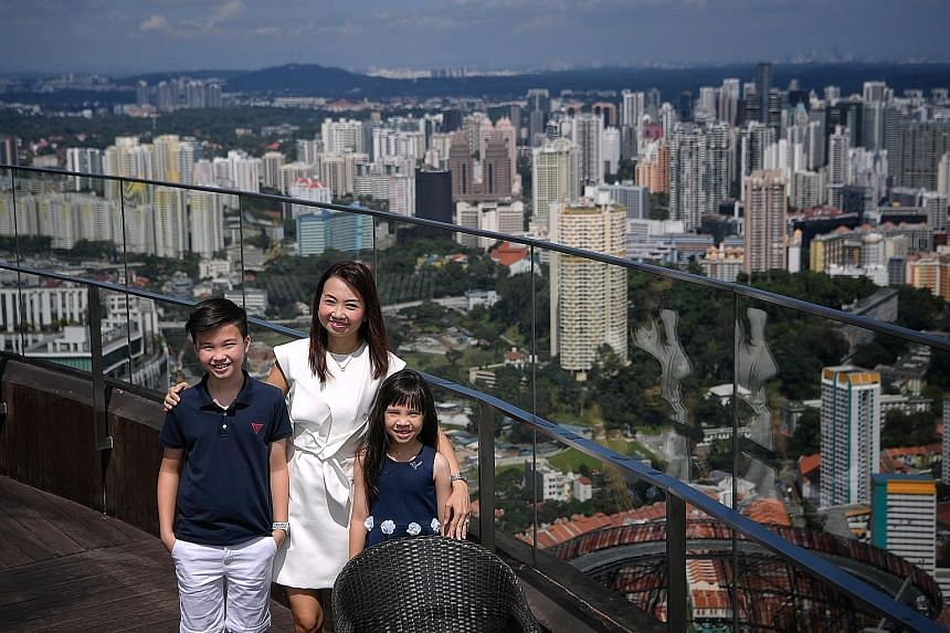 ERA division director Wendeline Goh, with her children - Brandon, 11, and Amelia, seven - at the rooftop of her condominium Skysuites@ Anson. She says the panoramic view of the city from her 68th-floor unit is breathtaking. Ms Goh says her apartment